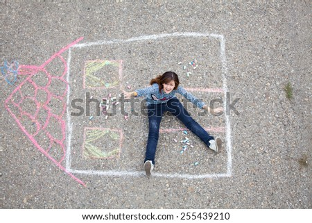 Happy girl sitting in drawn house - stock photo