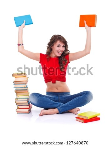 Happy girl sitting in the floor holding colorful books in hand - stock photo