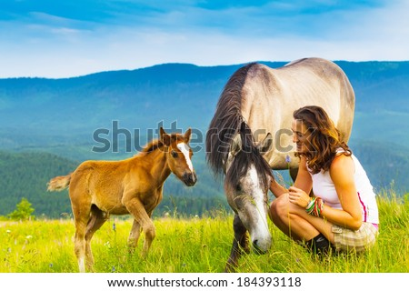 happy girl sitting on a green flower meadow near a wild horse and her calf. background of green hills - stock photo