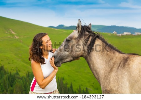 happy girl sitting on a green flower meadow near a wild horse and her calf. background of green hills