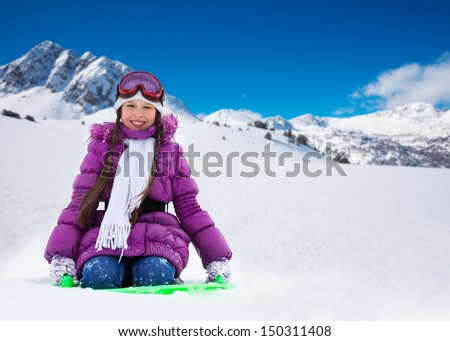 Happy girl sitting on sled with her hands lifted, wearing ski mask and purple coat, in the mountains