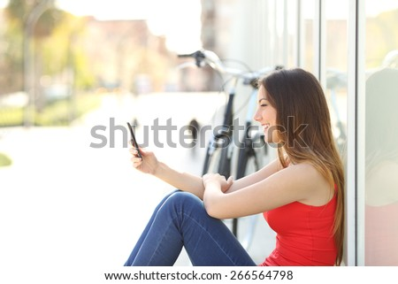 Happy girl sitting using a mobile phone in a park beside her bicycle - stock photo