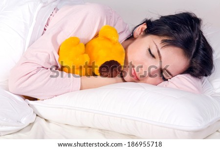 happy girl sleeping with teddy bear in bed - stock photo