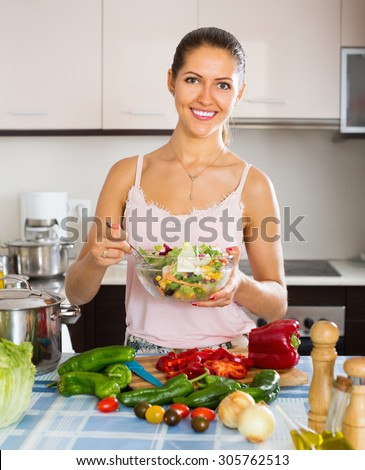 Happy girl standing at kitchen table with plate of salad