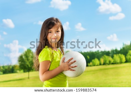 Happy girl standing in the park with volley ball smiling and looking at camera - stock photo