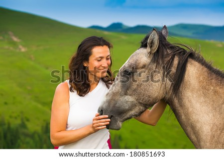 happy girl standing on green flower meadow near a wild horse background green hills and blue sky .