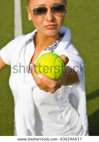 Happy girl stands with racket on court at sunny summer day