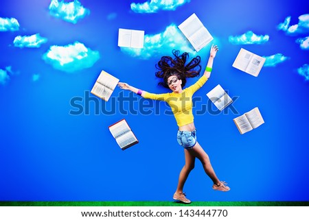 Happy girl student is flying in the sky with her books.