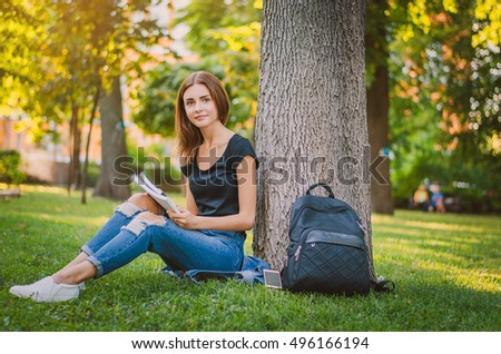happy girl student sitting on the grass near the tree in the park and reading. Education concept