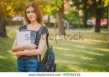 happy girl student with a backpack in a city park