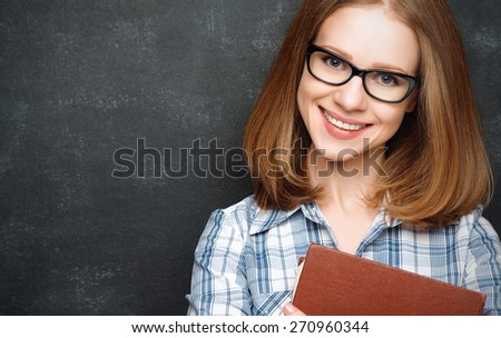 happy girl student with glasses and a book from the  blackboard - stock photo