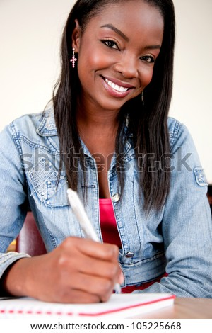 Happy girl studying in a classroom writing on her notebook - stock photo