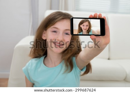 Happy Girl Taking Selfie With Mobile Phone - stock photo