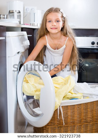Happy girl taking washed linen out washing machine - stock photo