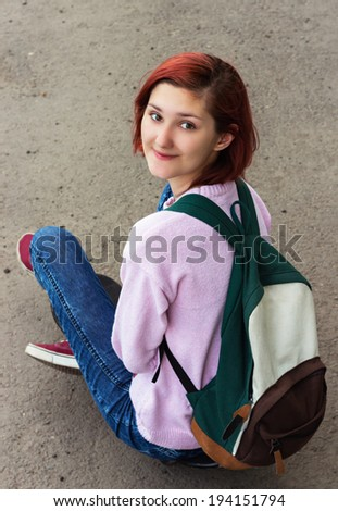 Happy girl teenager with a backpack sitting on the ground. - stock photo