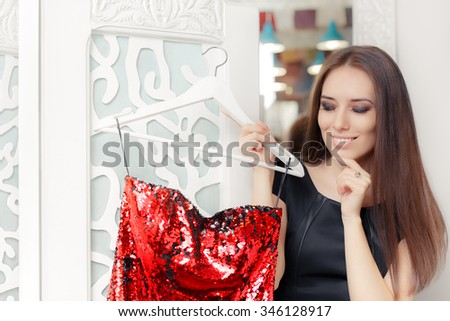 Happy Girl Trying on Red Party Dress in Dressing Room - Smiling fashion holding a clothes hanger with a fashionable garment
