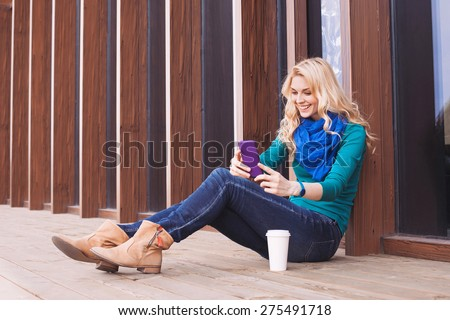 Happy girl using a smart phone in a city. - stock photo
