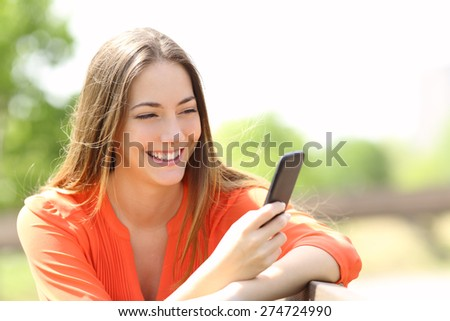 Happy girl using a smart phone in summer in a park - stock photo