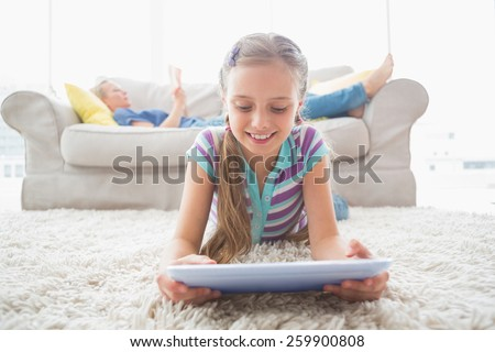 Happy girl using digital tablet on rug with mother reading book in background at living area - stock photo