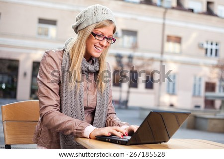 Happy girl using laptop in cafe - stock photo