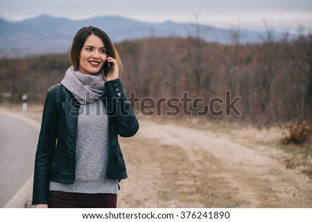 Happy girl using smartphone by the road.