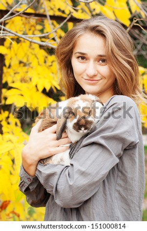 Happy girl walking in autumn park with her rabbit - stock photo
