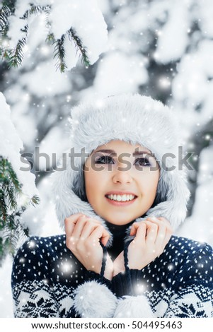 Happy girl walking in beautiful winter forest. Seasonal weather with blizzard and snowflakes. Christmas concept.