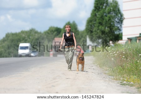 happy girl walking with dog - stock photo