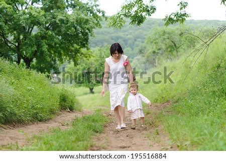 happy girl walking with her mother - stock photo