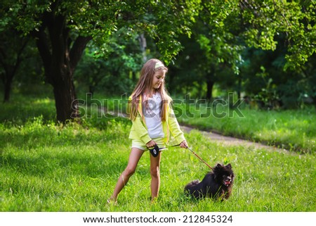Happy girl walking with her pomeranian doggy  - stock photo