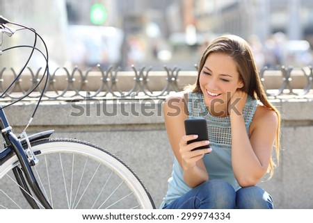 Happy girl watching media in a smart phone sitting in the street beside her bicycle - stock photo