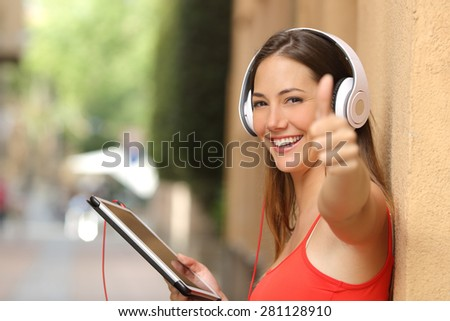 Happy girl wearing a red shirt with thumbs up using a tablet and listening music with headphones - stock photo