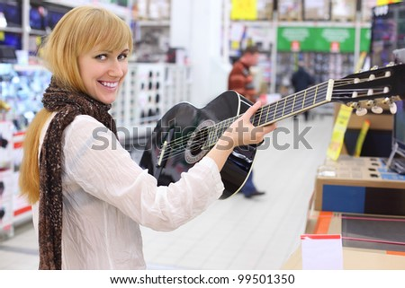 Happy girl wearing scarf holds guitar in supermarket; shallow depth of field - stock photo