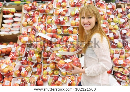 Happy girl wearing white shirt chooses packed apples in store; shallow depth of field - stock photo