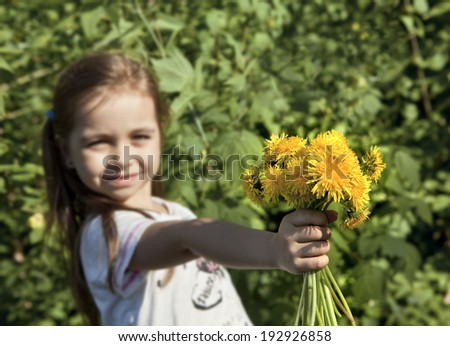 Happy girl with a bouquet of yellow dandelions. The focus of the bouquet. - stock photo