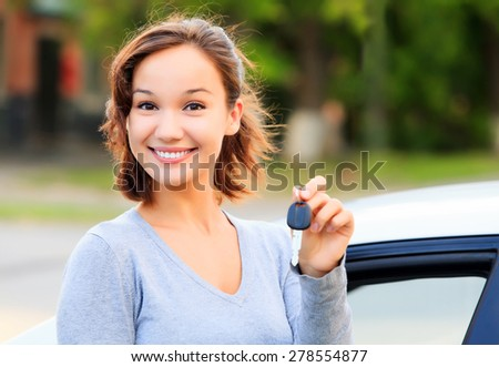 Happy girl with a car key smiling