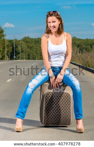 happy girl with a suitcase on the road on a sunny day - stock photo