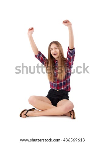 happy girl with arms up sitting on floor