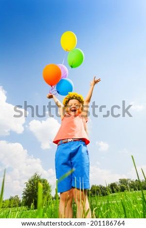 Happy girl with balloons wearing flower circlet - stock photo