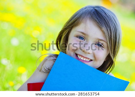 Happy girl with book outside  - stock photo