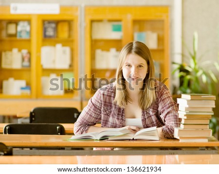 Happy girl with books at the library. looking at camera - stock photo