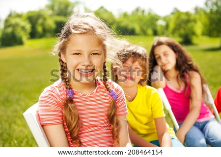 Happy girl with braids and her friends sitting - stock photo