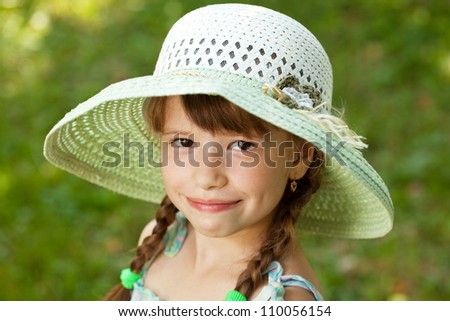 Happy girl with braids in the wide-brimmed hat