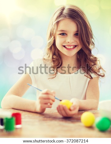 happy girl with brush coloring easter eggs - stock photo