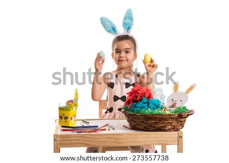 Happy girl with bunny ears showing painting Easter eggs against white background - stock photo