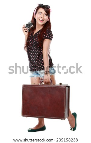 Happy  girl with camera and suitcase going on vacation. - stock photo