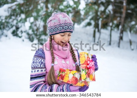 Happy girl with Christmas present in a winter forest. Girl opens a box with a gift, happy little girl open box with christmas present. Joyful girl in a pink jacket with two braids outdoors - stock photo