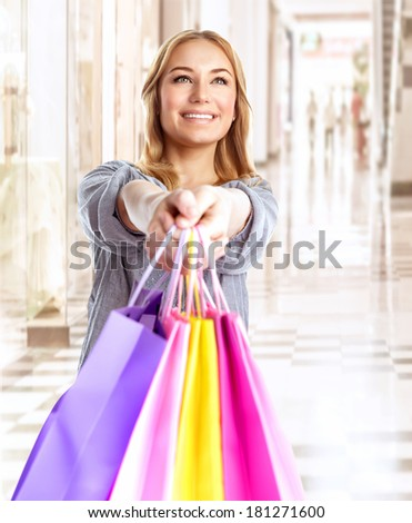 Happy girl with colorful shopping bag, cheerful young female doing purchase in great luxury retail store, spending money with pleasure concept - stock photo