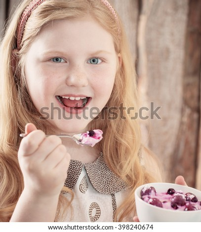 happy girl with dessert on wooden background - stock photo
