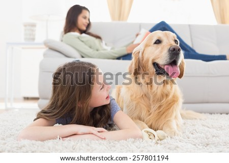 Happy girl with dog lying on rug while mother relaxing at home - stock photo